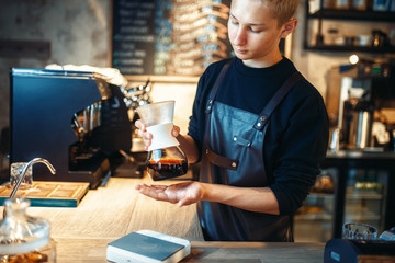 Young male barista makes fresh espresso in cafe