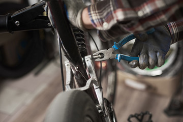 Cropped view of male mechanic working in bicycle repair shop, repairing bike using special tool, wearing protective gloves