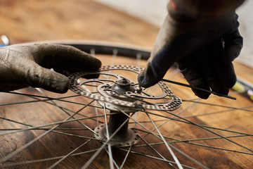 Cropped shot of mechanic making service in bicycle repair shop, repairing bike wheel using special tool, wearing protective gloves