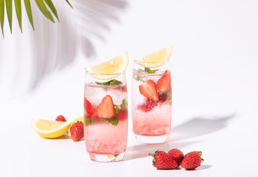 iced strawberry punch cocktail in glass with lemon on white background. summer drink.