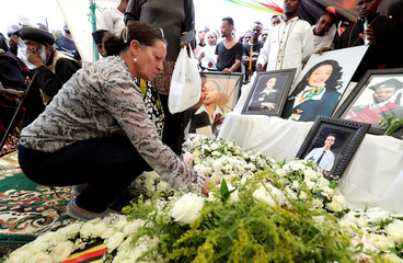 Annabelle Tayob puts flowers next to the portrait pictures of the victims of the Ethiopian Airlines Flight ET302 plane crash during the final mourning day to mark the 40th day in Gara Boka village, near Bishoftu town, southeast of Addis Ababa