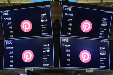 Screens display the company logo and trading information for Pinterest Inc. during the company's IPO on the front of the NYSE in New York