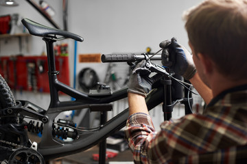 Cropped shot back view of professional mechanic working in bicycle repair shop, man repairing modern bike using special tool, wearing protective workwear and gloves