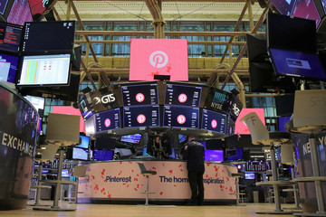 A trader works on the floor before the trading day as signage is displayed celebrating the IPO of Pinterest Inc. hangs on the front of the NYSE in New York