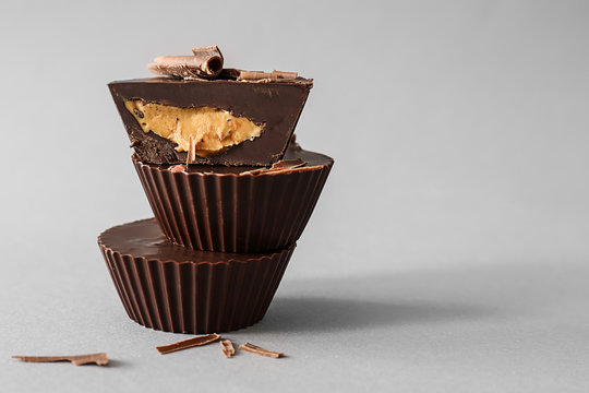 Tasty chocolate peanut butter cups on grey background