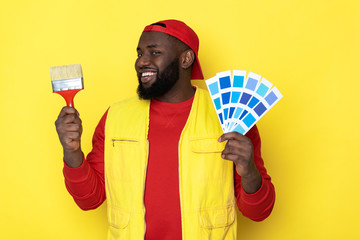 Profile of African man holding paintbrush and palette in arms
