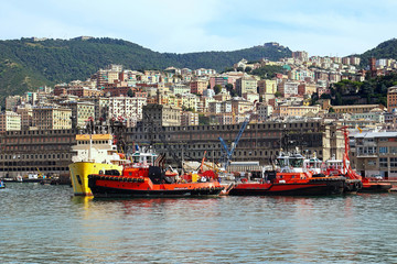 Tugboats in the Genoa harbor, sea view with cityscape
