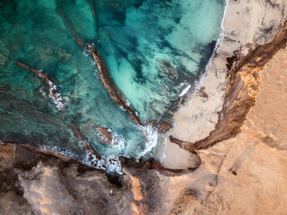 Aerial view of a car, parked at the edge of the cliff, of beautiful Fuerteventura's coastline