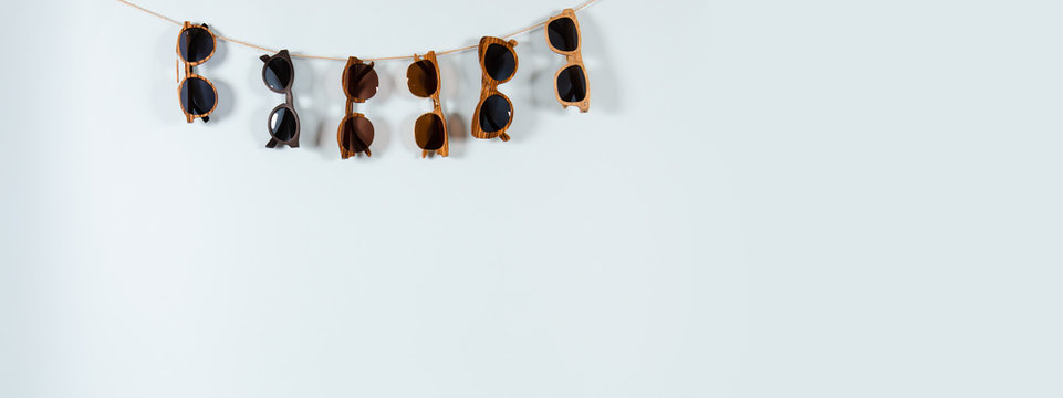 Sunglasses sale concept. Different sunglasses hanging on the rope on blue background. Fashion summer accessories. Copy space