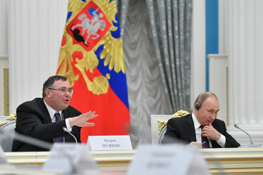Russian President Vladimir Putin listens to Total CEO Patrick Pouyanne during a meeting with French business leaders at the Kremlin in Moscow