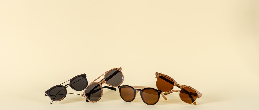 Wooden sunglasses of different design on yellow background. Copy space. Sunglasses sale concept. For banner optic shop