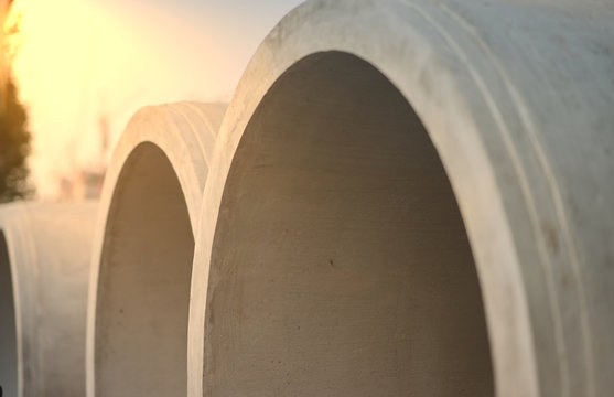 Big cement pipes in stack ,closed up with sunflare