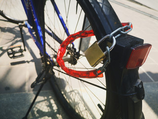 Red chain lock on bicycle wheels Parked on the side of the road