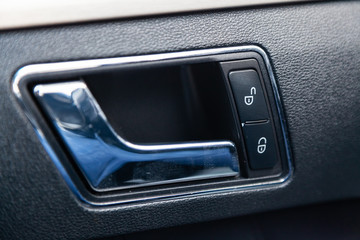 The interior of the car with a view of the door panel, handle and lock buttons with light gray trim