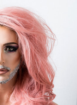Drag queen artist portrait with sparkly beard, long eyelashes,  eyebrows and pink hair isolated on white.