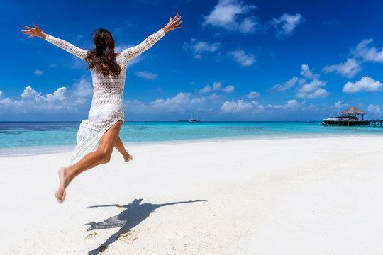 Glückliche Frau in weißem Sommerkleid läuft an einem tropischen Paradies Strand und genießt ihren Urlaub auf den Malediven