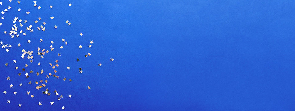 Holiday background with silver star confetti on blue background. Good backdrop for Christmas and New Year cards.