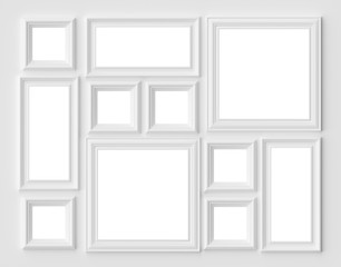 White picture or photo frames on the white wall with copy-space