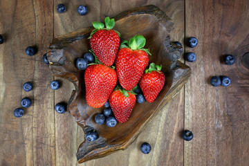 Overhead Display of Fresh Strawberries and Blueberries in a Rustic Wood Bowl