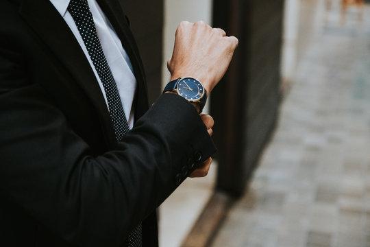 Crop elegant businessman in formal suit showing watch on blurred background
