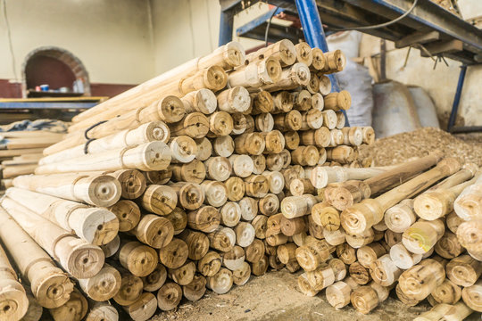 Pile of wooden sticks near sawdust and woodworking machine at workplace