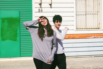 Young slim brunette guy and woman showing peace gesture in stylish cloths posing near building on street in sunny day