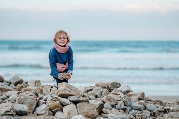 Positive kid holding rock near pile of stones on coast near waving sea on blurred background