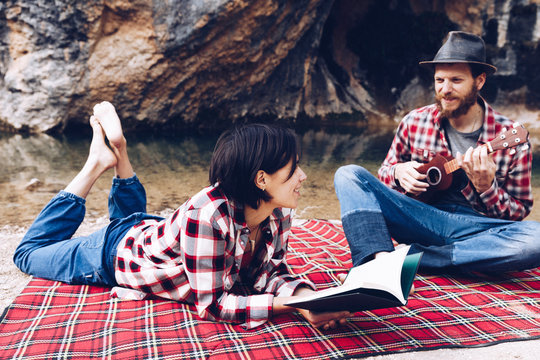 Adult man and woman on checkered plaid with book and small ukulele having picnic on lake shore
