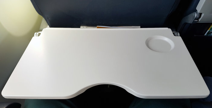 Airplane tray table on seat back for put food on when eating or writing