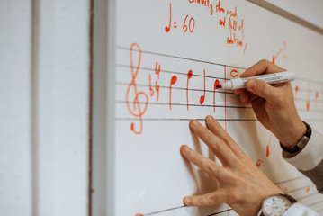 Unrecognizable man hands writing music notes in a white board at a conservatory school
