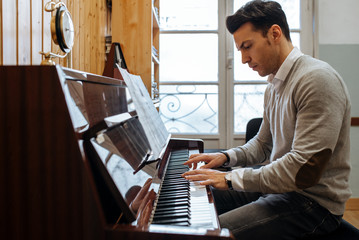 Handsome man playing piano during rehearsal in recording studio.