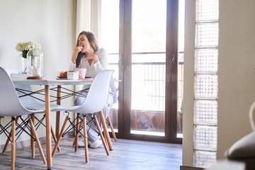 Attractive young happy woman having breakfast at table near window at home