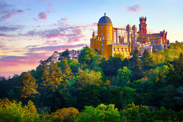 National Palace of Pena in Sintra, near Lisbon, Portugal. Picturesque landscape with dawn and green trees. Blue morning sky with clouds. Fotomurales