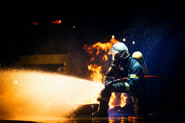 Unrecognizable male in firefighter uniform suppressing fire with heavy stream of water