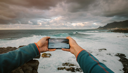 First person view of a man taking a picture with phone at a seashore landscape