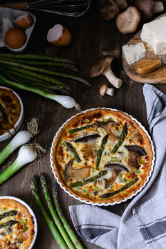 Baked homemade quiche pie with asparagus and mushrooms in white ceramic form on wooden background, Flat lay