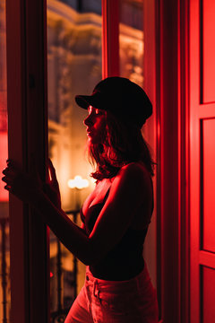Side view of young slim woman in cap standing near balcony in room in redness at night