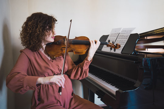 Woman sitting next to a piano playing a violin