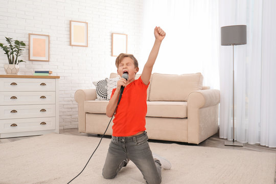 Cute boy singing in microphone at home