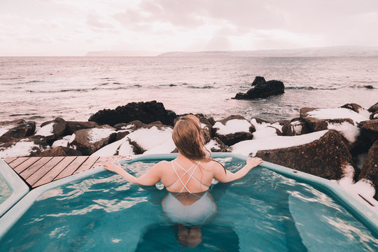 Young woman with closed eyes resting in water of pool near rocks and cloudy sky