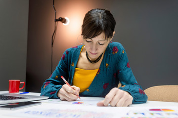 Beautiful female in elegant outfit making notes of graphs while sitting at desk in modern office