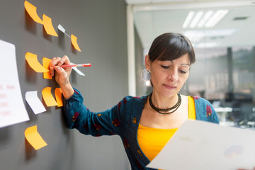 Side view of adult female holding paper sheet with charts and writing on sticky notes while standing near gray wall in office