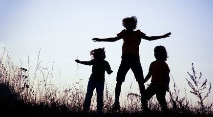 Children playing jumping on summer sunset meadow silhouetted