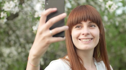 A girl makes selfie in the garden. An attractive red-haired woman smiles making selfi using a mobile phone in a cherry orchard. The concept of using gadgets for a healthy lifestyle.