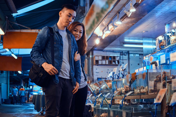 Young asian couple looking for something special at traditional chainese market Fototapete