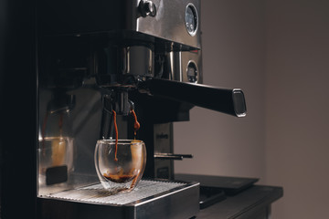 Fresh espresso coffee pouring in a glass cup