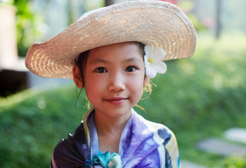 Asian little girl with hat in the garden in the sun