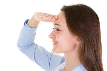 Cheerful young woman is trying to see something hand forehead