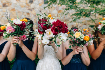 Bride and Bridesmaids Hiding Their Faces Behind Bouquets