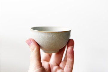 Fingers holding a beautiful japanese tea cup